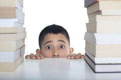 Worried student with books. Portrait of worried teenage boy behind books Royalty Free Stock Images