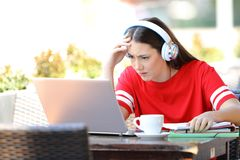 Worried student e-learning with a laptop in a coffee shop royalty free stock photography