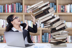 Worried student with fall books in library. Young student of business management hold a pile of falling books in the library Stock Photo