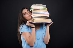 Worried student girl holding a pile of books royalty free stock photography