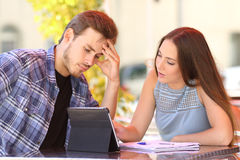 Worried student learning with a friend teaching Stock Image