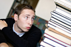 Worried Student Looking At Books. A worried student looks up at the high pile of textbooks he has to go through to do his homework assignment Stock Photography