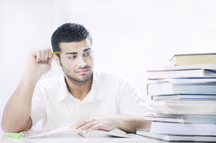 Worried student looking books on white background. Concept of concern Royalty Free Stock Photos
