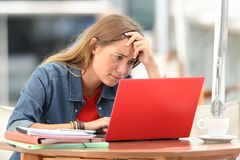 Worried student searching on line in a laptop. Single worried student searching on line content in a laptop sitting in a coffee shop outdoors royalty free stock image