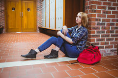 Worried student sitting on the floor against the wall. At the university stock photo