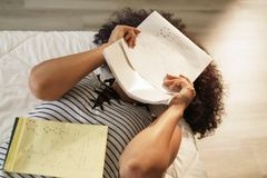 Worried Student Studying Chemistry For College Homework. African american college student doing homework in bed at home. Black woman studying chemistry formulas royalty free stock images