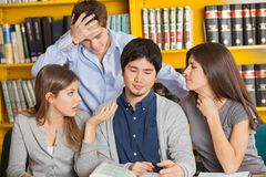 Worried Students With Book Sitting In Library Stock Image
