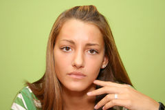 Worried teen. Age girl looking at you and isolated on green background Stock Photo