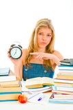 Worried teen girl pointing on alarm clock Stock Photo