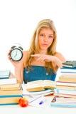 Worried teen girl pointing on alarm clock Stock Photo