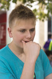 Worried teenage boy. With close cropped blond hair staring down at the ground with his hand to his mouth in a close up portrait Royalty Free Stock Photos