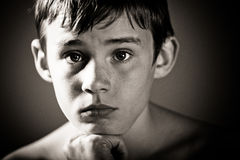 Worried Teenage Boy with Head Resting on Chin. Black and White Head and Shoulders Close Up of Young Shirtless Teenage Boy Staring at Camera with Worried Royalty Free Stock Images
