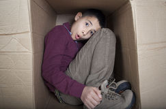 Worried teenage boy sitting in cardboard box Royalty Free Stock Photography