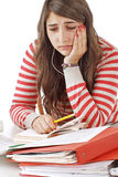 Worried teenage girl with piles of school books Stock Photo