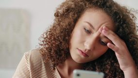 Worried teenage girl using a smart phone at home. Worried teenage girl using a smart phone in her room stock video