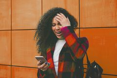 Worried teenager girl looking at her smart phone in a park with an unfocused background Stock Images