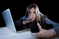 Worried teenager using mobile phone and computer as internet cyber bullying stalked victim abused Royalty Free Stock Photo