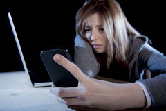 Worried teenager using mobile phone and computer as internet cyber bullying stalked victim abused Royalty Free Stock Images