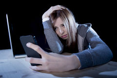 Worried teenager using mobile phone and computer as internet cyber bullying stalked victim abused Royalty Free Stock Image