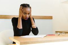 Worried thoughtful African or black American businesswoman holding her pretty face with hands, closing ears Stock Image