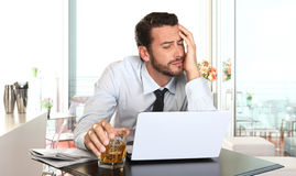 Worried and tired businessman in crisis working on computer. Laptop at bar table in stress under pressure facing work problems Stock Photo