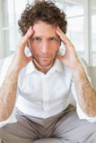 Worried well dressed man sitting with head in hands Stock Photos