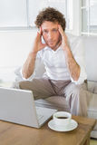 Worried well dressed man sitting with laptop at home Royalty Free Stock Images
