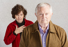 Worried Wife. Concerned senior women with hand on chest behind sad man Stock Images