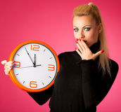 Worried woman with big orange clock gesturing delay, rush, nervo. Us, stress because of lack of time Stock Images