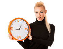 Worried woman with big orange clock gesturing delay, rush, nervo Stock Photos