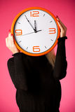 Worried woman with big orange clock gesturing delay, rush, nervo. Us, stress because of lack of time Royalty Free Stock Images
