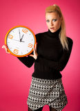Worried woman with big orange clock gesturing delay, rush, nervo. Us, stress because of lack of time Stock Photos