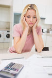 Worried woman with bills and calculator in kitchen Royalty Free Stock Photos