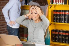 Worried Woman Biting Lip While Looking At Laptop. Worried young women biting lip while looking at laptop in college library Stock Photography
