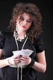 Worried woman calculating her bills. Shopping over black background Royalty Free Stock Images