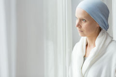 Worried woman with cancer. Wearing blue scarf and white bathrobe stock image