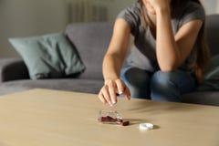 Worried woman catching antidepressant pills. Close up of a worried woman catching antidepressant pills at home Stock Photos