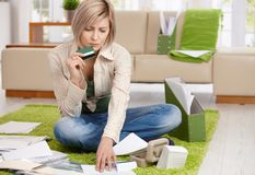 Worried woman checking documents. Holding credit card, sitting on floor with crossed legs at home Stock Photography