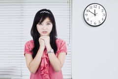 Worried woman with clock in office Stock Photo