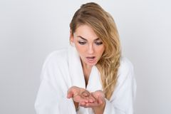 Worried woman holding loss hair Stock Photography