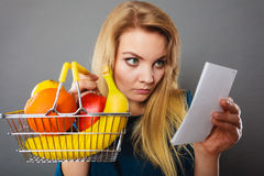 Worried woman holding shopping basket with fruits Stock Photo