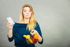 Worried woman holding shopping basket with fruits Stock Images