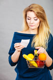 Worried woman holding shopping basket with fruits Stock Photos