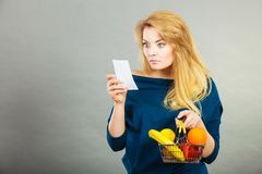 Worried woman holding shopping basket with fruits royalty free stock photo