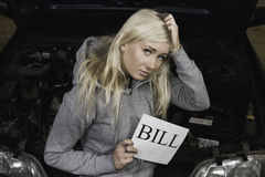 Worried woman holding sign in garage Royalty Free Stock Photo