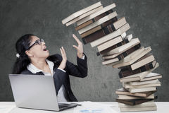 Worried woman holds a falling books Stock Images