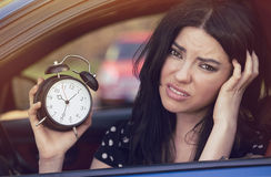 Worried woman inside car showing alarm clock running late to work. Worried woman sitting inside her car showing alarm clock running late to work stock image