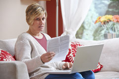 Worried Woman on laptop. Woman sitting at home with laptop looking worried at camera while holding a bill stock images