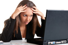 Worried Woman Looking At A Computer Monitor. Worried businesswoman looking at a computer screen, isolated in white Royalty Free Stock Image
