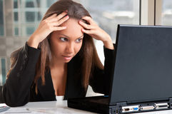 Worried Woman Looking At A Computer Monitor. Worried businesswoman looking at a computer screen in an office Royalty Free Stock Images